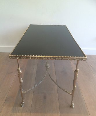 vintage coffee table with black glass top and hoof-shaped feet